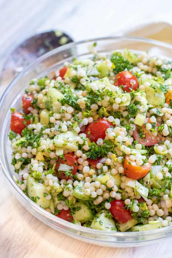 a bowl of couscous with tomatoes and cucumbers and parsley.