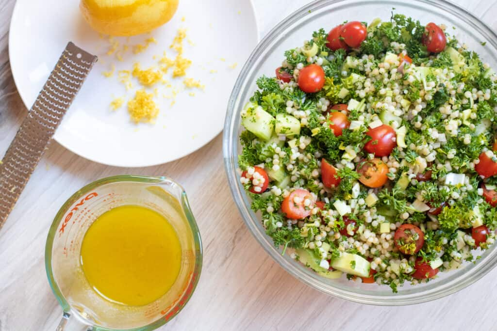 a bowl of cucumbers, parsley, couscous, cucumbers and a vinaigrette and zested lemon.