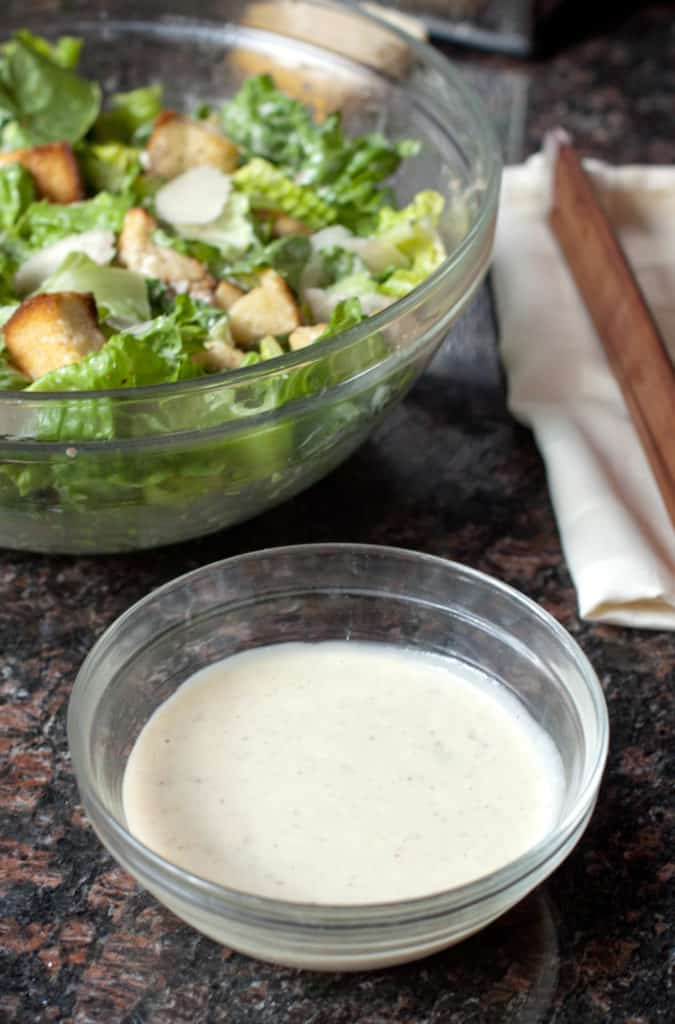 a small bowl of dressing in front of a big bowl of caesar salad.