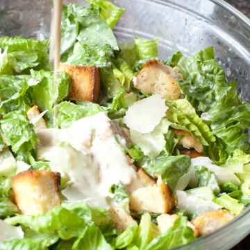 a large bowl of salad with dressing being poured in.