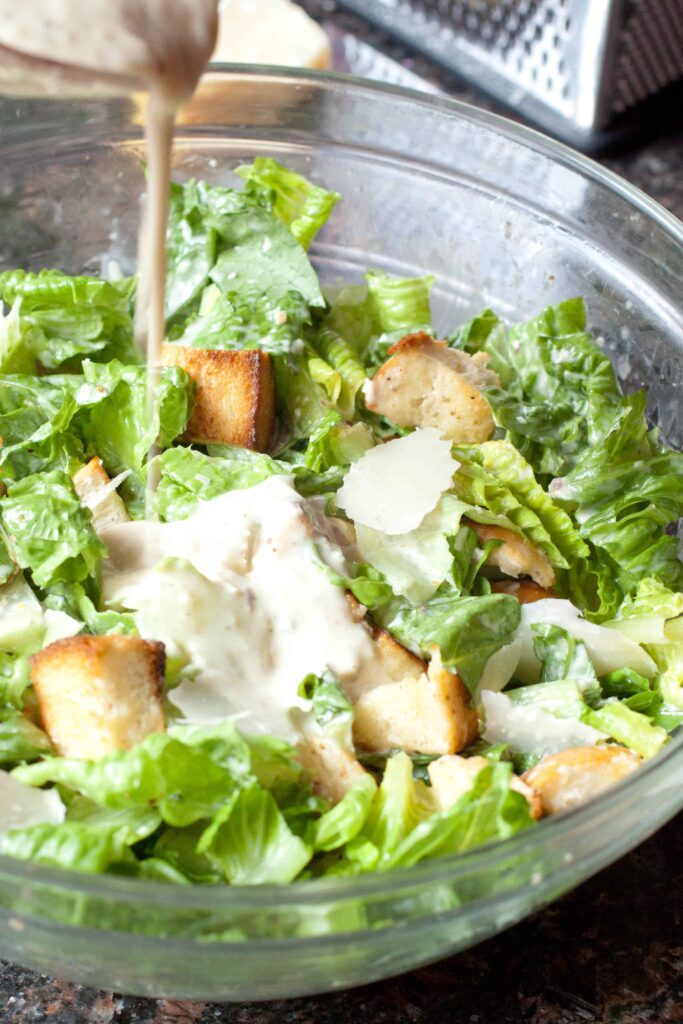 Caesar dressing being poured into a bowl of salad.