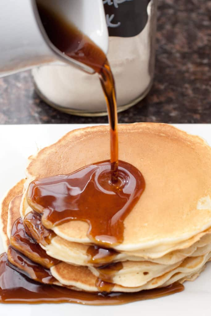 syrup being poured on a stack of pancakes.