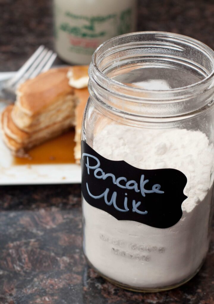 a jar of homemade pancake mix with cooked pancakes in the background