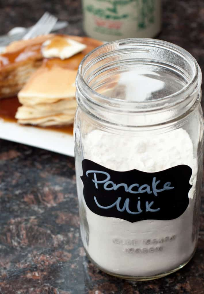 a jar of pancake mix with pancakes in the background
