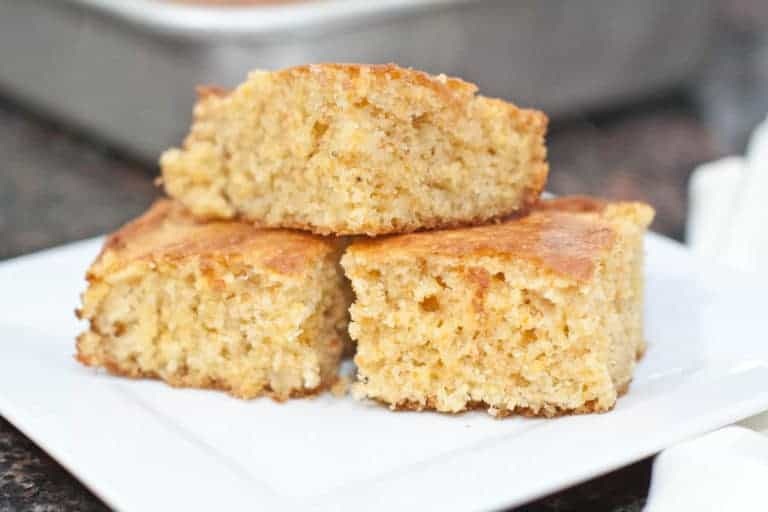 3 pieces of cornbread stacked on a plate.