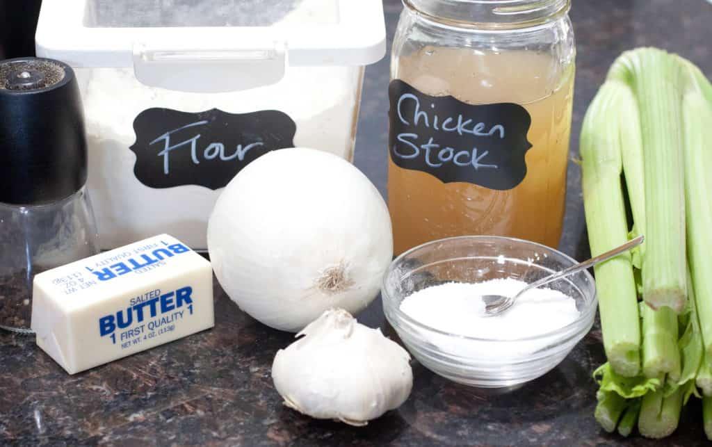 flour, chicken stock, celery, butter, pepper, onion, garlic, and salt on counter