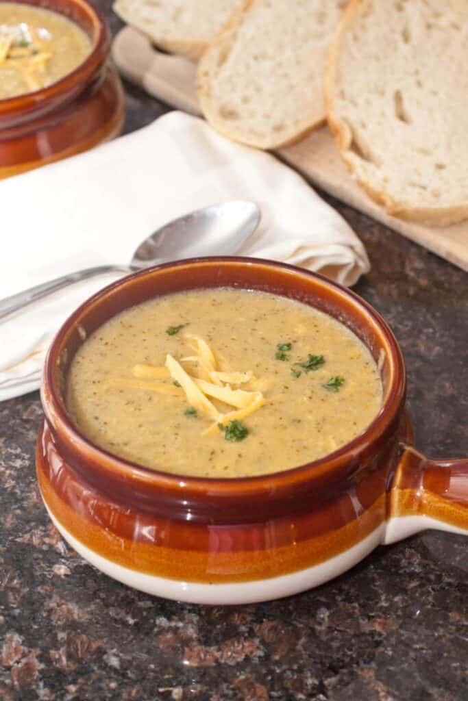 a soup crock with cheddar broccoli soup next to sliced bread.