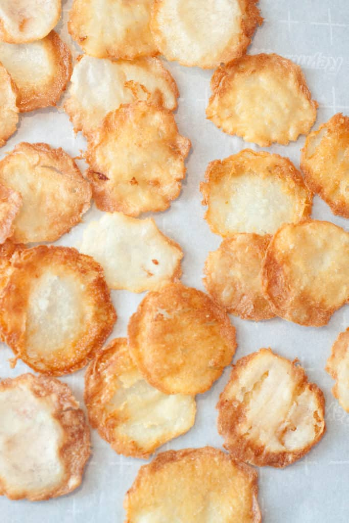 fresh made potato chips on parchment paper.