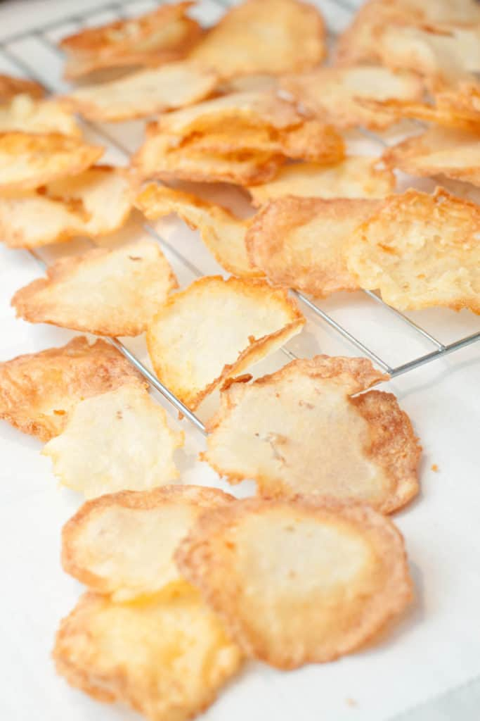 fresh fried chips cooling on a cooling rack