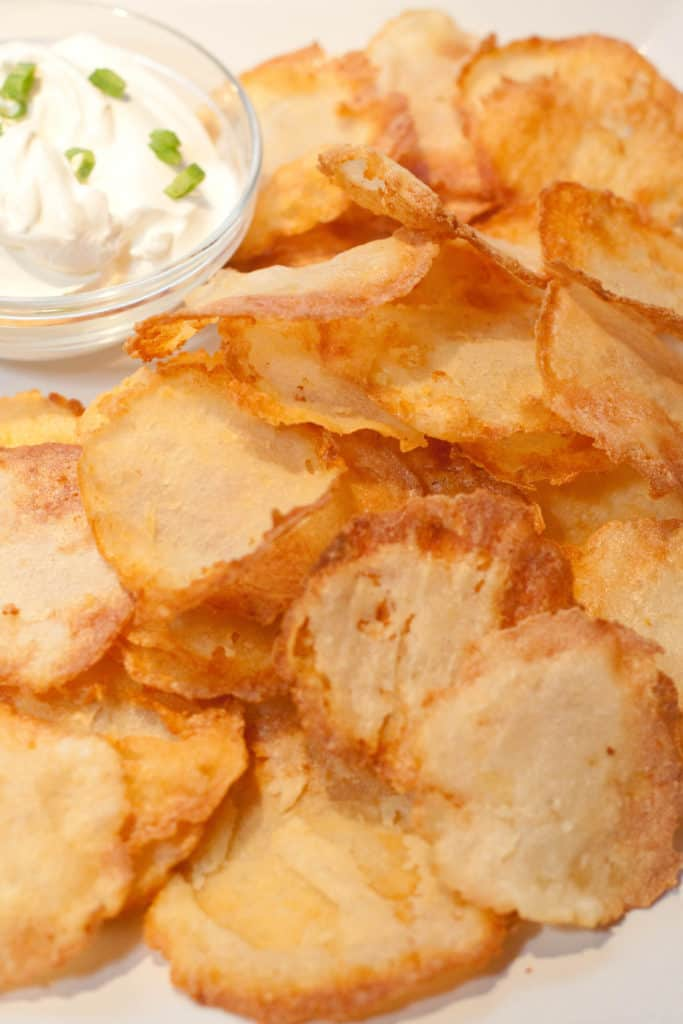 a plate of crispy chips with a bowl of dip