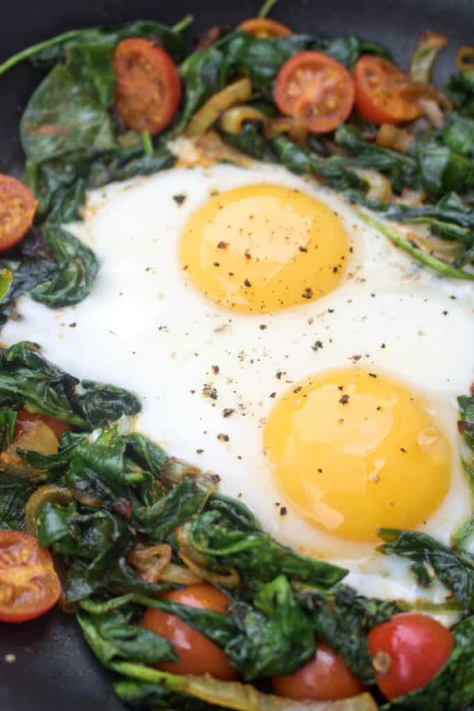 a pan with sauteed spinach, tomatoes, onions, and eggs