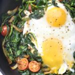 a pan with spinach, tomatoes, onions, and eggs