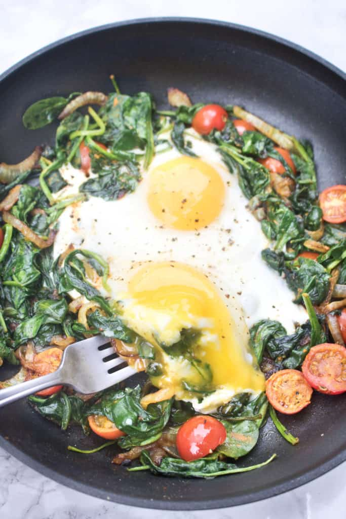 a pan with sauteed spinach, tomatoes, onions, and eggs with runny yolk