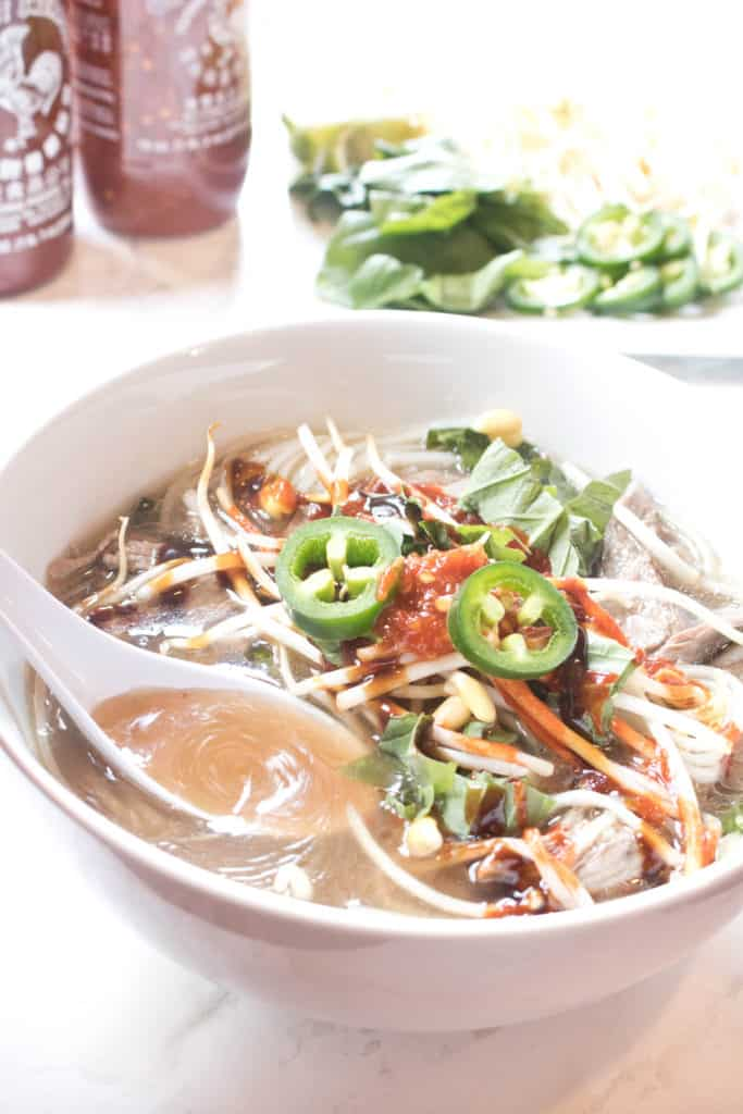a bowl of beef pho with a spoon ladeling broth