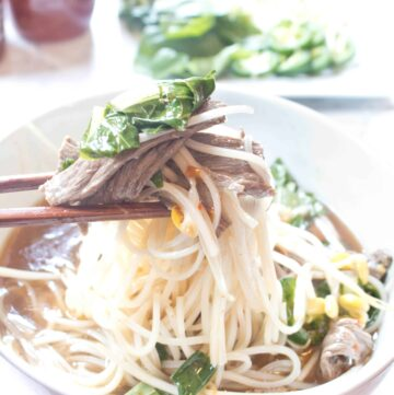 a bowl of beef pho with chopsticks holding a bite up