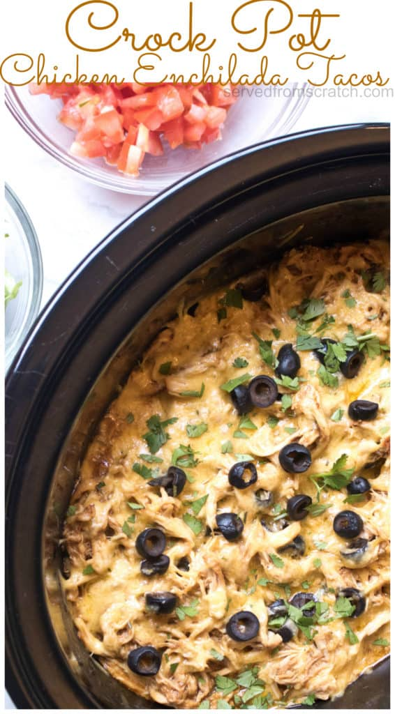 crock with shredded chicken enchilada topped with cheese and sliced olives