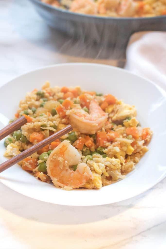 cauliflower shrimp fried rice in a bowl with chopsticks