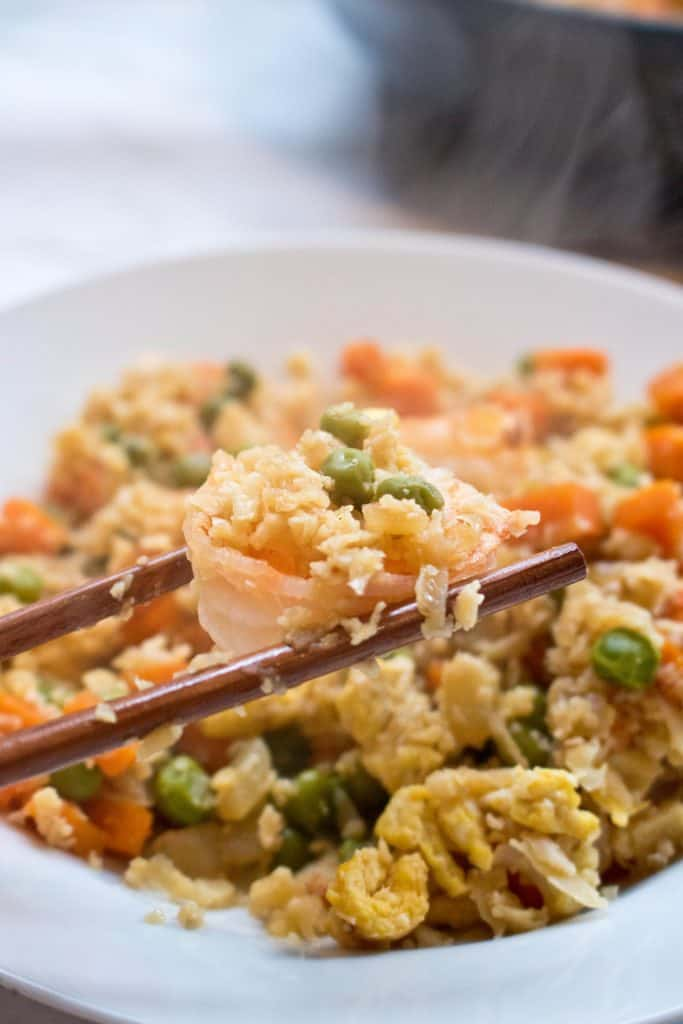 cooked cauliflower shrimp fried rice in a bowl held by chopsticks.