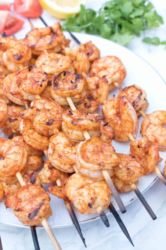 skewers with grilled shrimp on a plate.