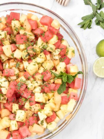 a bowl of pineapple, watermelon, and mint.