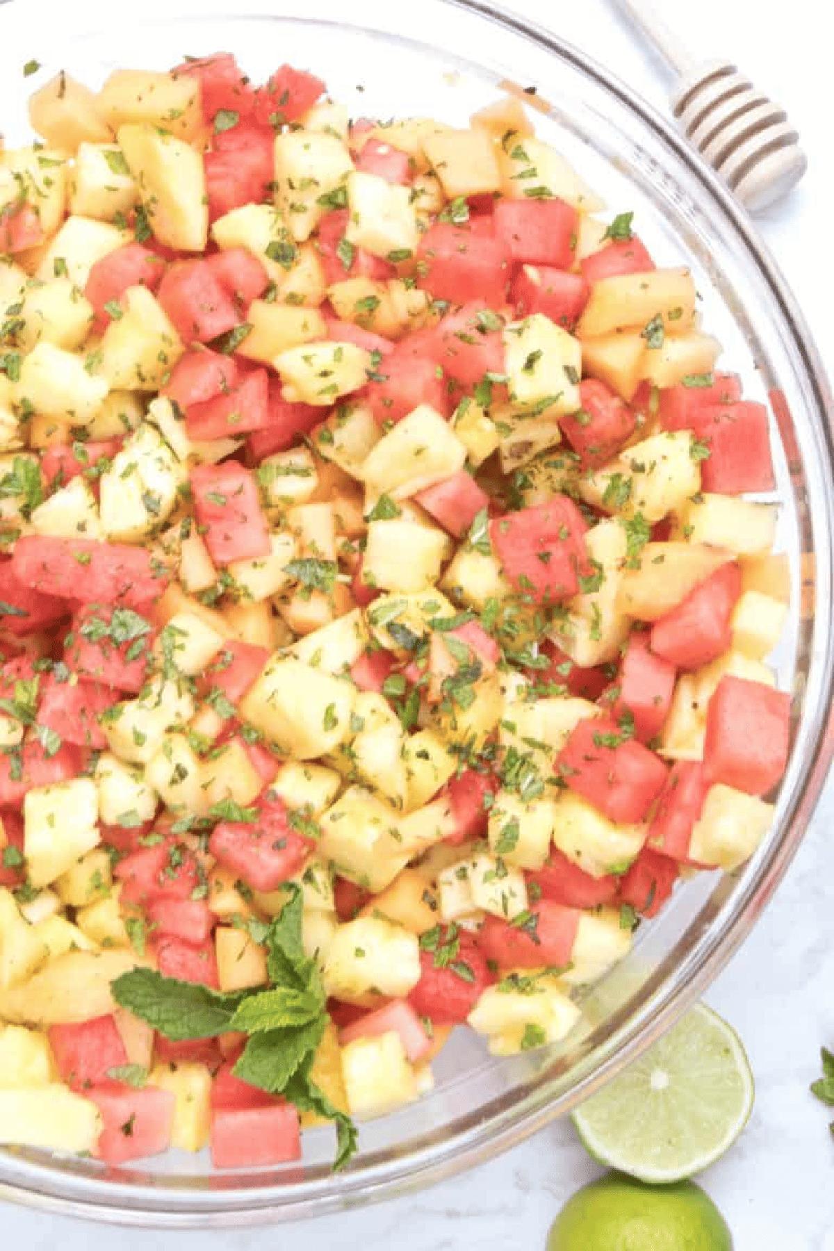 Cantaloupe, pineapple, melon, limes, mints, honey on a counter.