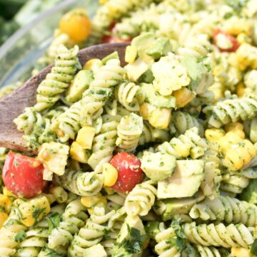 wooden spoon in a large bowl of green pasta salad.
