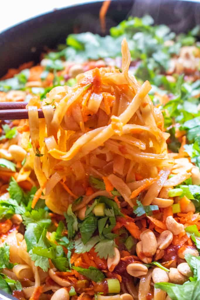 chopsticks holding up some noodles in a pan with carrots and cilantro and peanuts.