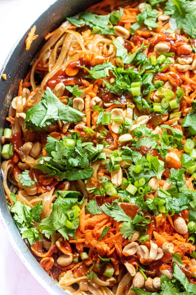 a pan with noodles, carrots, cilantro, and peanuts.