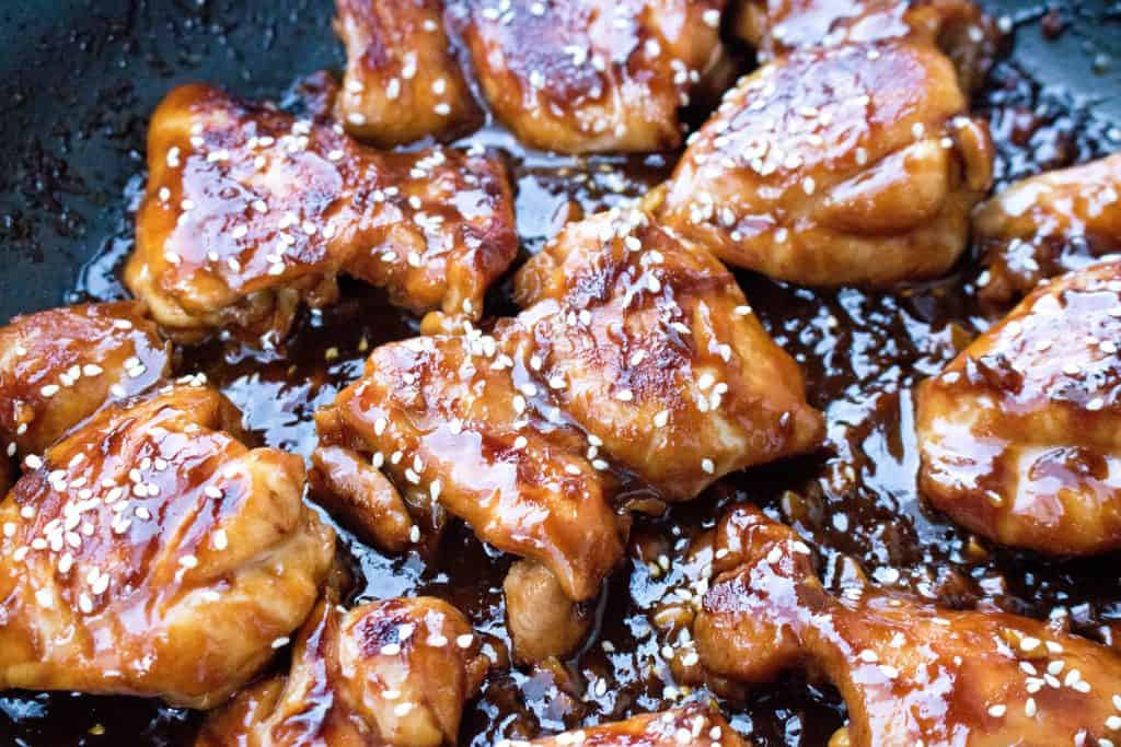 A pan of cooked chicken thighs in a thick sauce with sesame seeds