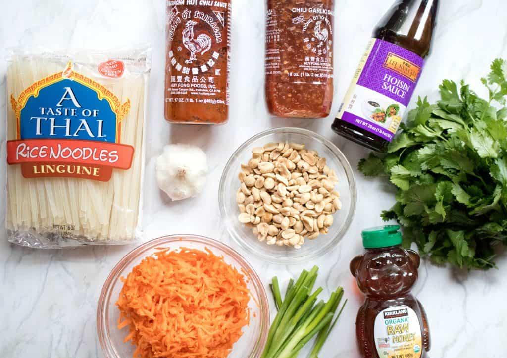 noodles, carrots, honey, peanuts, hoisin, cilantro, garlic chili sauce, garlic, green onions, and sriracha on counter.