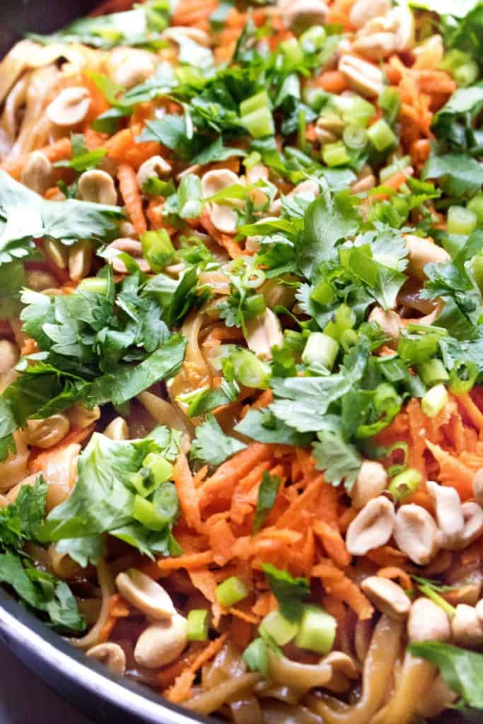 a close up of a pan of cooked noodles with carrots, peanuts, and fresh cilantro.