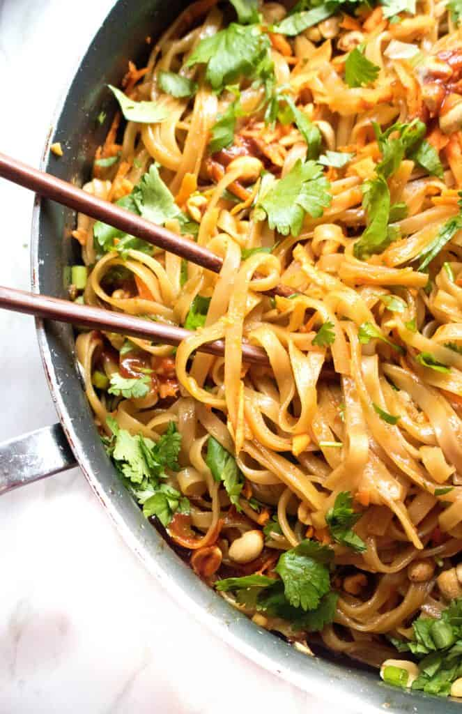 a pan of cooked noodles with peanuts, carrots, and fresh cilantro.