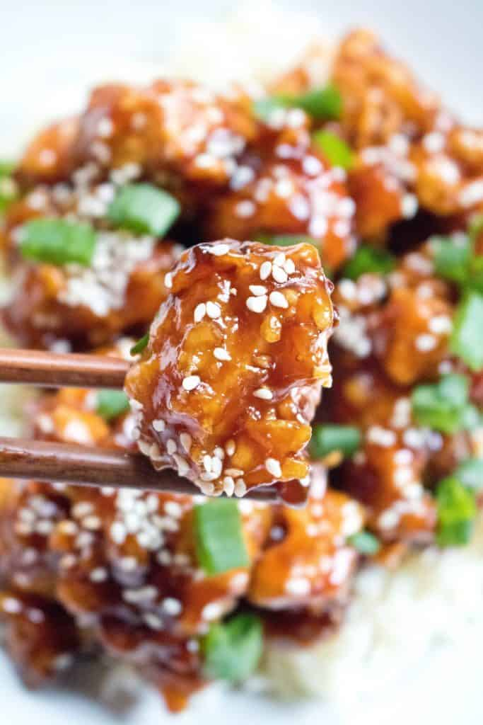 sesame chicken held by chopsticks over a plate of sesame chicken
