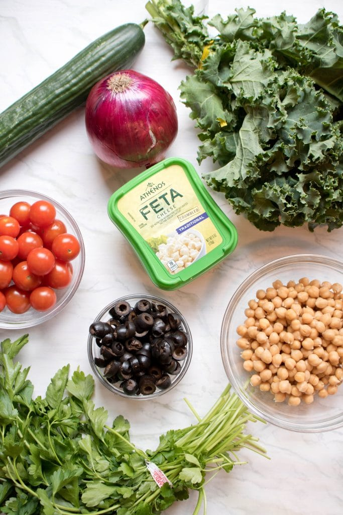 Tomatoes, Feta, olives, cucumbers, tomatoes, kale, and chickpeas and onion on a counter.