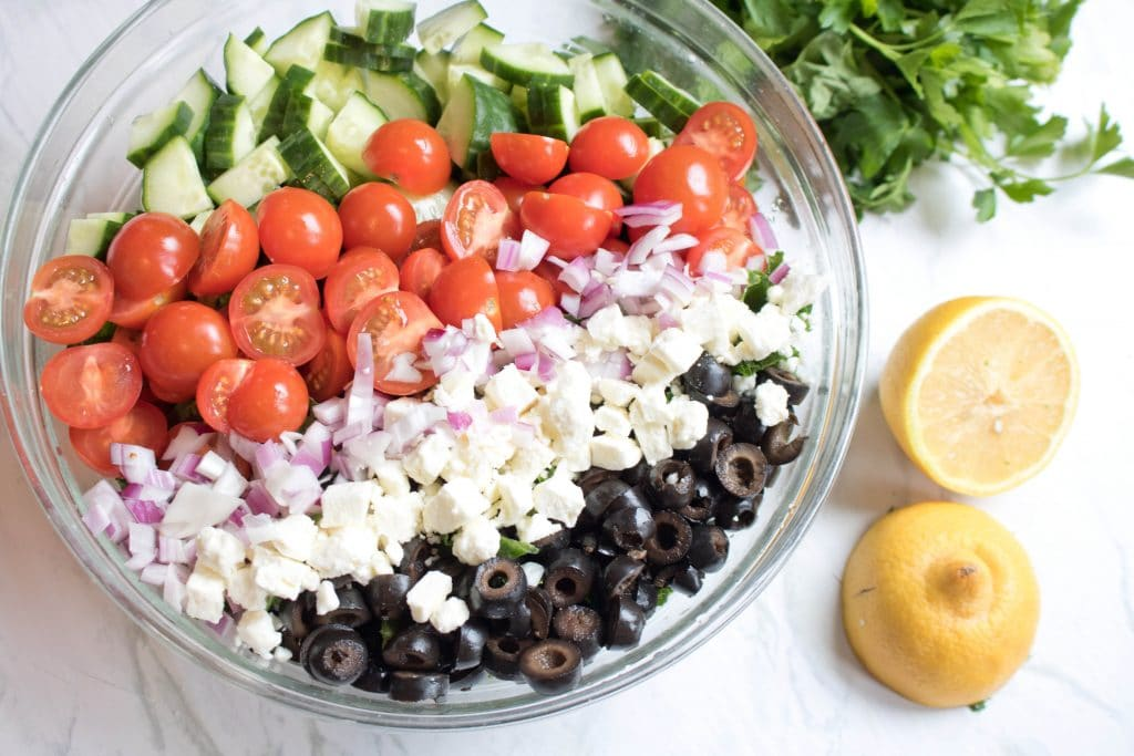 bowl with kale, tomatoes, cucumbers, feta, and chickpeas.