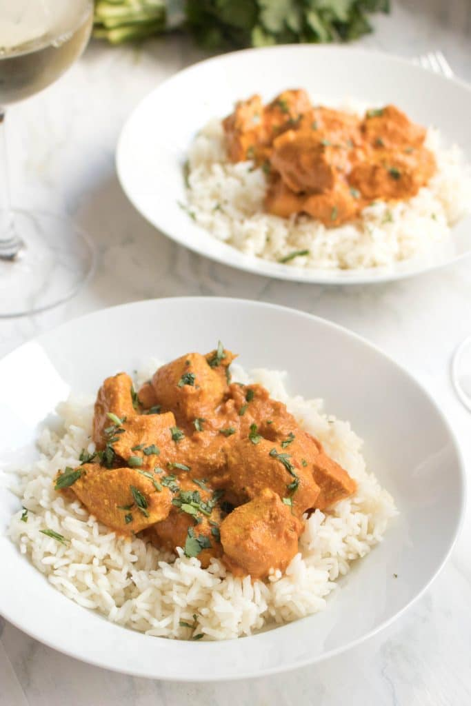 Chicken Tikka Masala on a bed of white rice in two bowls on counter