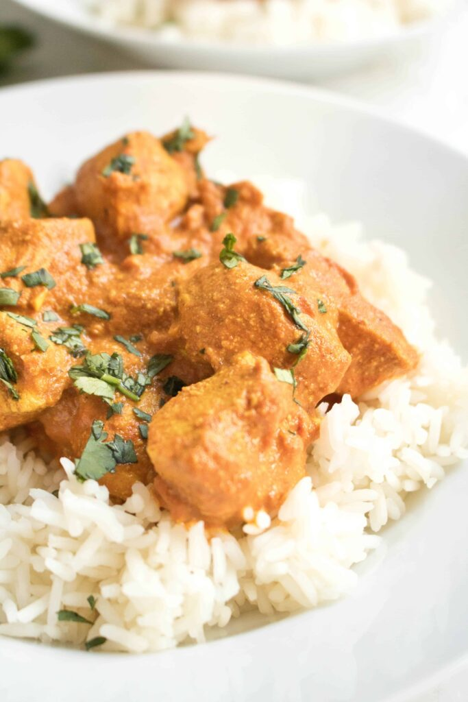 Chicken Tikka Masala on a bed of white rice in a bowl
