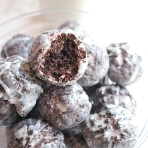 Easily made at home from scratch, these Copycat Glazed Chocolate Munchkins are the perfect snackable little donut hole!