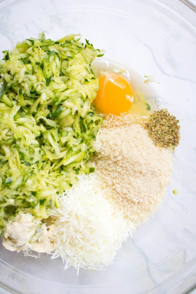 a bowl with shredded zucchini, egg, panko breadcrumbs, cheese, and spices.