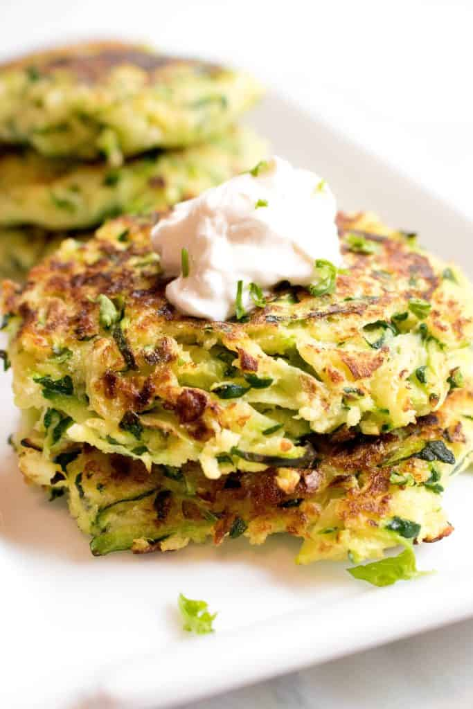 stacked zucchini fritters topped with sour cream on a plate.