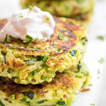 a close of up of stacked zucchini fritters topped with sour cream