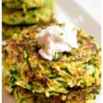 stacked cooked zucchini fritters topped with sour cream