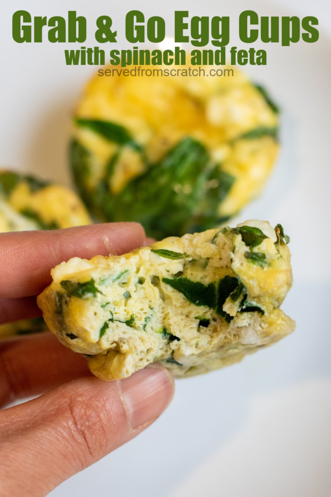 a hand holding a spinach egg cup with a bite taken out and pinterest text.