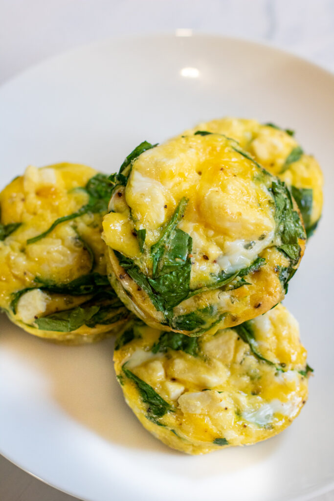 a plate of cooked egg cups with spinach