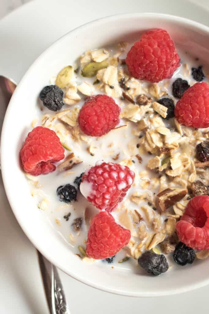 An overhead of a bowl of muesli with fresh raspberries