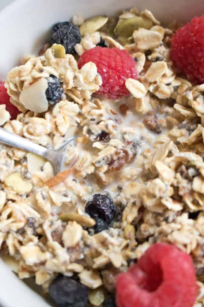 A close up of muesli with milk and a spoon