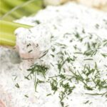 dill onion dip with a celery stick in it