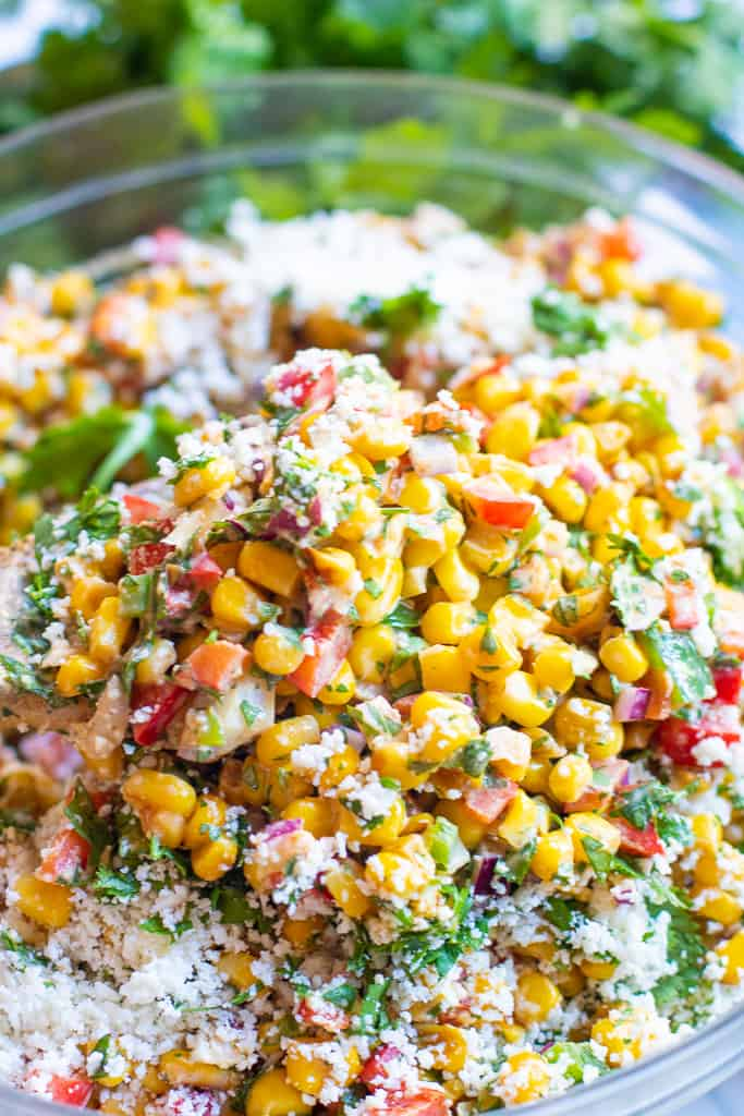 a bowl of corn salad with red pepper, cilantro, and shredded cheese.