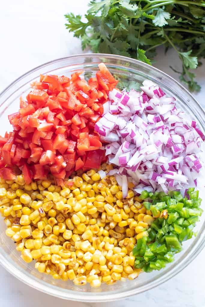 a large bowl of diced tomatoes, onions, corn, and jalapeno.