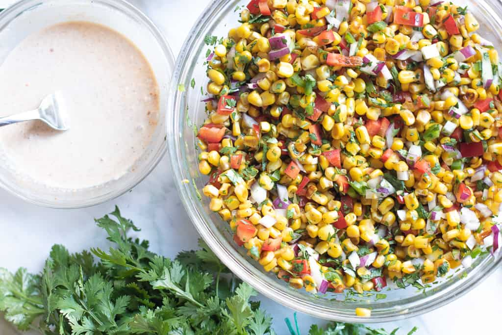 Mexican street corn salad dressing in a bowl next to mixed veggies.